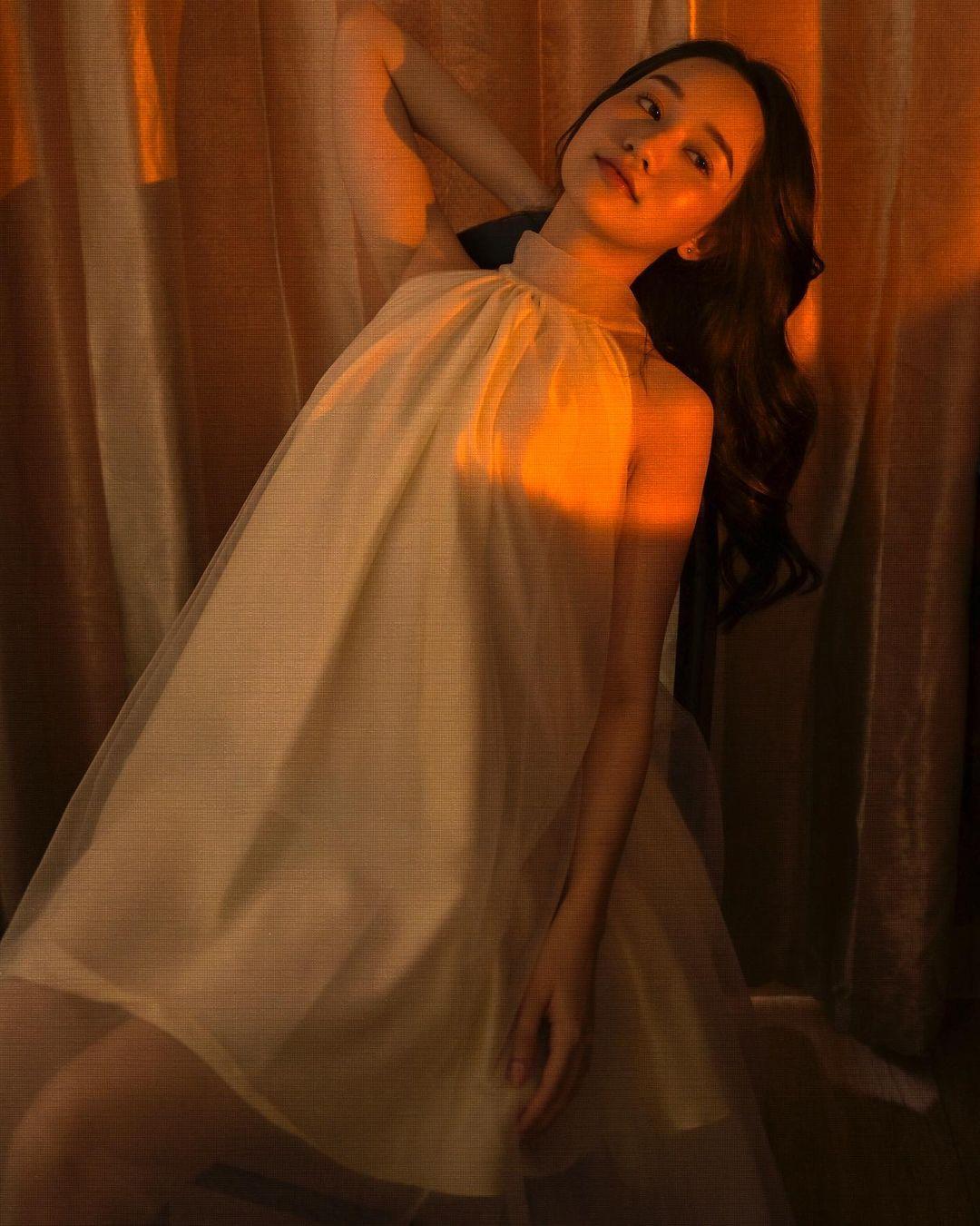 cách tạo dáng chụp ảnh đẹp khi mặc váy bằng việc Chạm tay vào tóc nhẹ nhàng